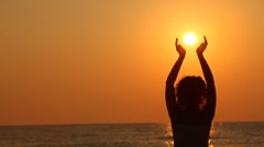 Woman standing on beach, holding sun in her hands - stock footage