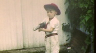 Stock Video Footage of Cute BOY WITH TOY POP GUN Cowboy Hat 1950s Vintage Film Retro 8mm Home Movie