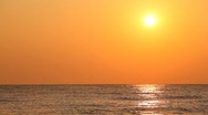 Stock Video Footage of Sunset against orange sky over quiet sea waves