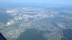 View on landscape of settlement and forest from window of flying plane Stock Footage