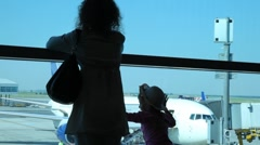 Silhouettes of woman with daughter look through window at planes at airport Stock Footage