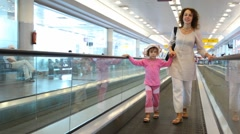 Woman and girl run on speedwalk at airport Stock Footage