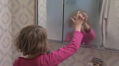 Girl (7-8) drawing heart on foggy bathroom mirror Stock Footage