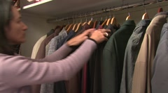 Woman choosing her coat from closet Stock Footage