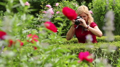 Woman taking photos of plowers in the garden, close up Stock Footage