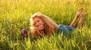 Young adult with flowers lying in the grass-1. Dolly Stock Footage