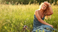 Young adult with flowers sitting in the grass. Dolly Stock Footage