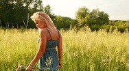 Pretty young adult walking in the meadow. Dolly. Stock Footage
