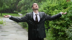 Business man in rain, holding up arms Stock Footage
