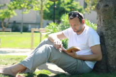 Young handsome man reading book in park Stock Footage