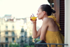 Woman drinking orange juice on the balcony - stock footage