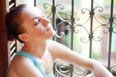 Young sad woman sitting near the window Stock Footage