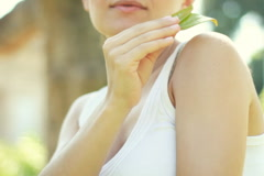 Young woman gently touching the skin with leaf Stock Footage