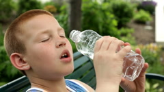 Boy pouring bottle of water into mouth Stock Footage