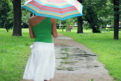 Woman with colorful umbrella jumping over the puddles, slow motion Stock Footage