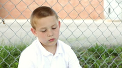 Boy sitting against fence looks at camera Stock Footage