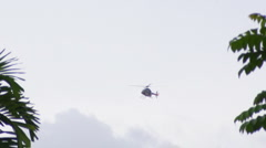 119 Police Helicopter comes out from behind trees Stock Footage