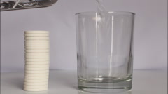 Glass of water with effervescent tablet - stock footage