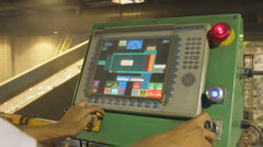 HANDS WORK TOUCHSCREEN AT RECYCLING PLANT Stock Footage