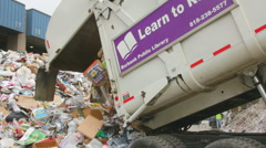 GARBAGE TRUCK DUMPS RECYCLABLES Stock Footage