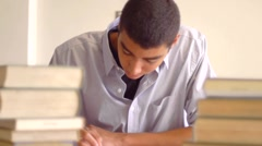 Male student writing with piles of books - stock footage