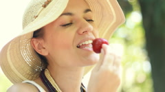 Young attractive woman eating strawberry outdoor Stock Footage
