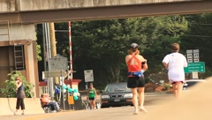 Runners on side of road as car moves through(HD)c Stock Footage