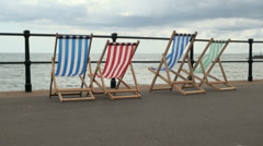 Empty Striped Deck Chairs on a Cloudy Day Stock Footage