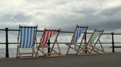 Empty Deck Chairs on Dull Stormy Clouds Day Stock Footage