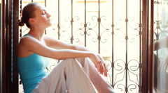 Young sad woman sitting near the window - stock footage
