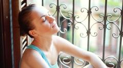 Young sad woman sitting near the window - stock footage