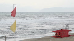 HD: Red and Yellow Flags in front of Rough Sea Stock Footage