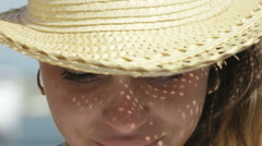 Woman in straw hat smiling at camera - stock footage