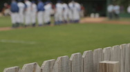 Stock Video Footage of Base ball team on field during national anthem, blurred then focus on fence line