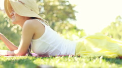 Young woman eating apple while lying on the grass in park, dolly shot Stock Footage