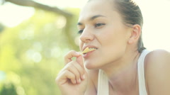 Young woman eating chips outdoors HD Stock Footage