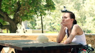 Young sad woman sitting by the table in the park HD Stock Footage