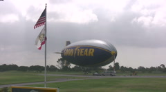 Long shot of Good Year Blimp with American flag in foreground Stock Footage
