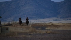 Two cowboys riding horses at sunset with mountains in background  (HD) Stock Footage