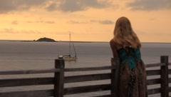 Women leaning on fence looking out over the ocean Stock Footage