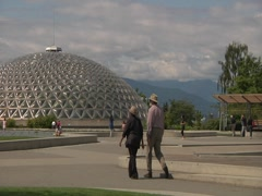 Couple walking with glass dome and  mountains in the background Stock Footage