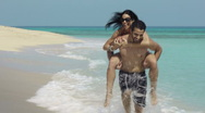 Piggyback ride with happy man and woman on the beach Stock Footage