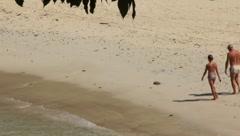 Stock Video Footage of Couple Walking Along Beach Shore Line (HD) cc