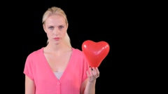 Young woman popping heart shaped balloon Stock Footage