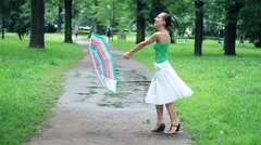 Young happy woman rotates in the park with colorful umbrella, slow motion Stock Footage
