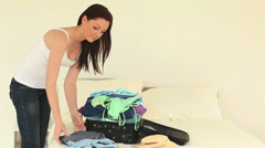 Good looking brunette woman packing up her suitcase Stock Footage