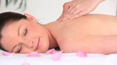 Portrait of a good looking dark-haired woman receiving a massage while lying on Stock Footage