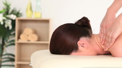 Young dark-haired woman receiving a massage while lying on a massage table - stock footage
