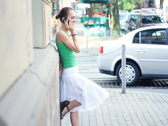 Woman standing by the wall and talking on mobile phone in the city NTSC Stock Footage