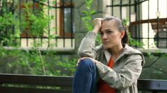 Sad woman sitting on bench in the park, steadicam shot HD Stock Footage